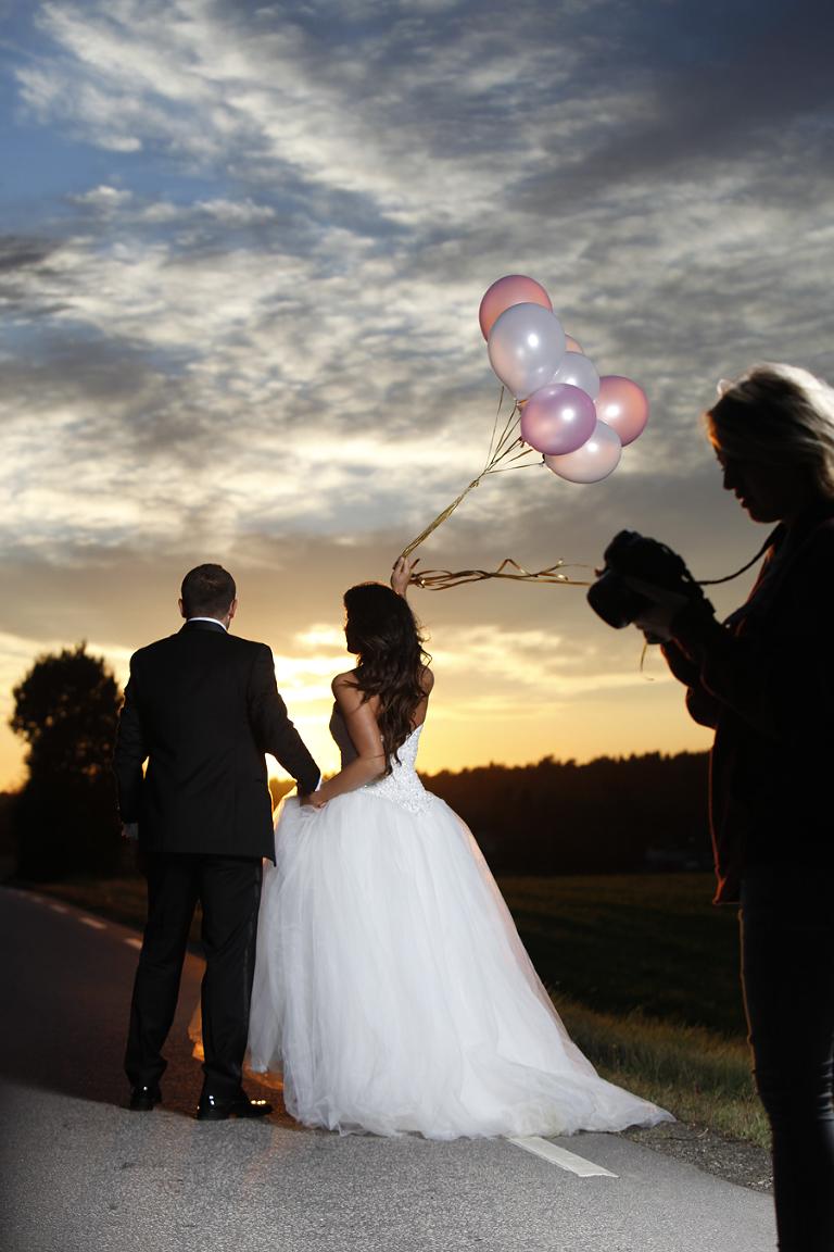 Her studerer Jeanett bildene på sitt kamera. Blitsen fra studiolamen slår inn på brudeparet som går langs veien.