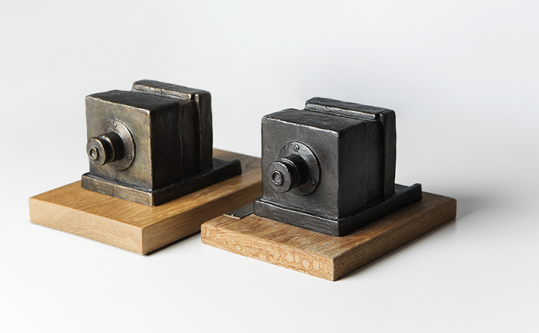 Begge disse skulpturene har vi hatt i vårt fotostudio. Den ene av disse har vi til odel og eie etter å ha vært beste fotograf fem år på rad. Bronsestatuene er en kopi av kameraet til louis daguerre fra 1839.